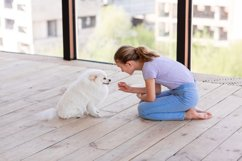Cute teenage girl training her spitz dog at home Product Image 13