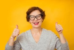 Portrait of elderly woman showing thumbs up Product Image 1