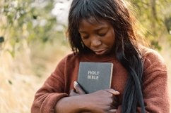 Christian afro girl holds bible in her hands Product Image 1