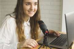 A blogger records a podcast into a microphone at home. Product Image 1