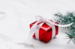 New Year and Christmas present in red wrap with white ribbon Product Image 1