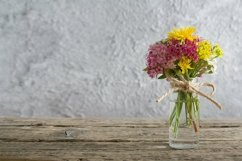 Miniature glass bottle with wildflowers copy space Product Image 1