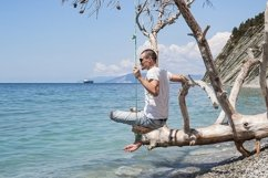 A guy is sitting on a swing made of a fallen tree. 2pcs Product Image 1