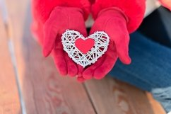 Small red heart on white rattan heart in woman hand Product Image 1