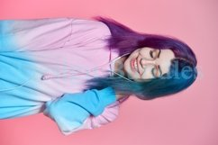 Girl listening to music on headphones on a pink background Product Image 7