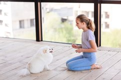 Cute teenage girl training her spitz dog at home Product Image 8