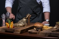 Uniformed chef serves a meat dish on a wooden tray Product Image 1