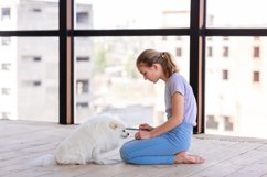 Cute teenage girl training her spitz dog at home Product Image 3
