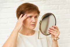 Unhappy aged woman looking in mirror at home Product Image 1
