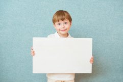 Young boy holding white blank board on blue background Product Image 1