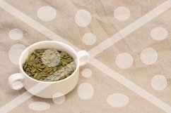 pumpkin seeds, in a white cup on natural linen. pumpkin seed Product Image 1