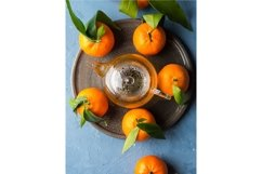 Winter tea in pot and tangerines on blue backgound Product Image 1