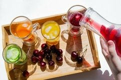 Colorful drinks, cherries. Decanter pours red juice, shadows Product Image 1