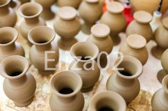 small brown earthenware jars stand in a row Product Image 1