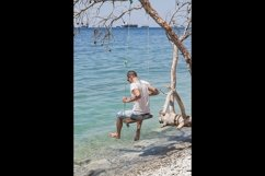 A guy is sitting on a swing made of a fallen tree. 2pcs Product Image 2
