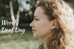 world deaf day text. small hearing aid in the ear of a woman Product Image 1