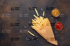 French fries in a paper bag with sauces Product Image 1