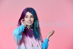 Girl listening to music on headphones on a pink background Product Image 5
