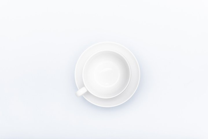 white porcelain cup on a saucer isolated on a white