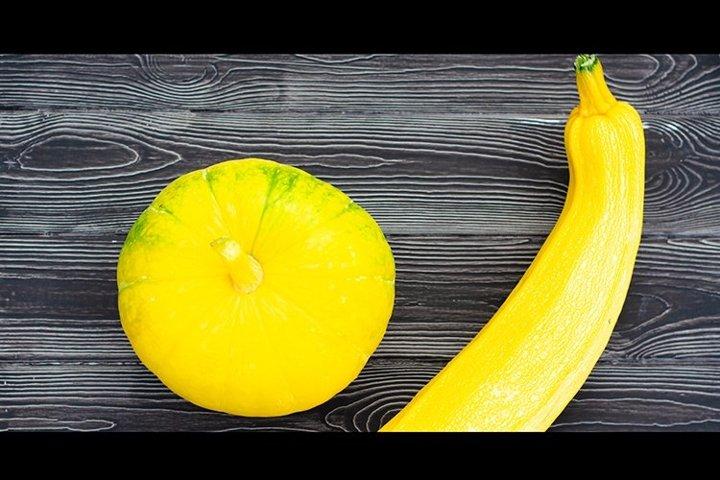 Yellow Pumpkin and zucchini on a dark wooden background.