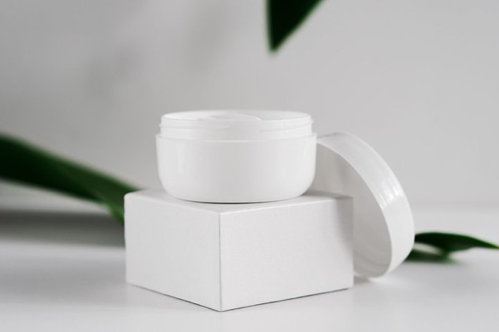 Natural cosmetic cream jar and greenery side view