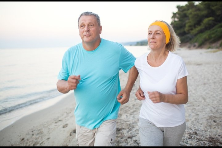 Senior couple jogging on the coast