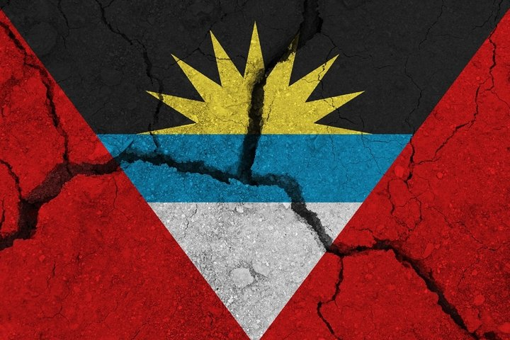 Antigua and Barbuda flag on the cracked earth.
