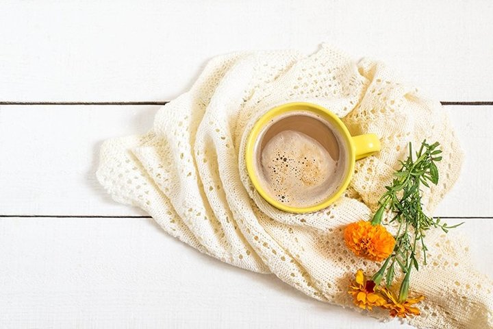 Coffee with milk, knitted scarf and flowers tagetes