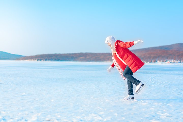 Young beautiful woman in red coat and figure skates