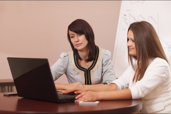Two women sitting at a table with a laptop