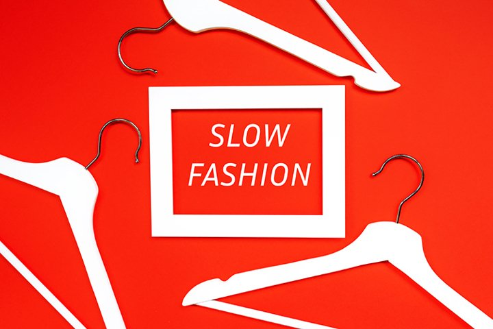 Slow Fashion-text in a white frame on a red background with