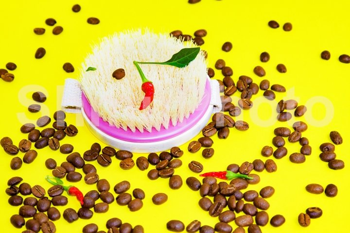 Body brush, coffee beans and pepper on yellow background