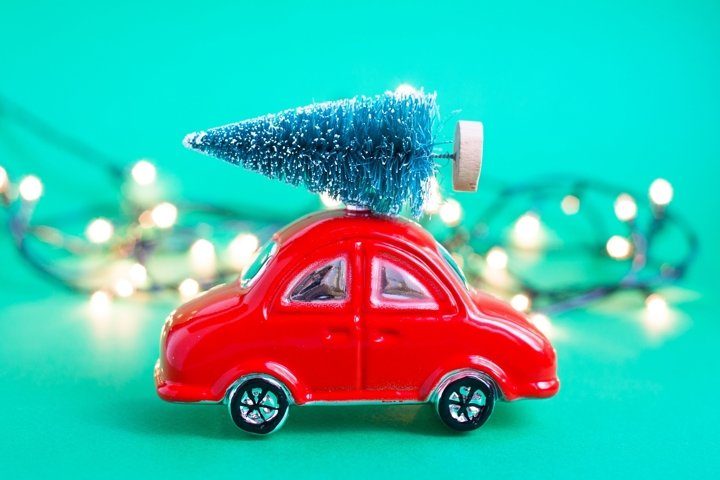 Red toy car with fir tree and garland with lights