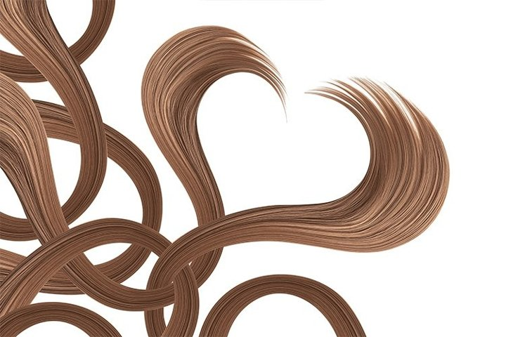 Heart made by natural brown hair on white, isolated