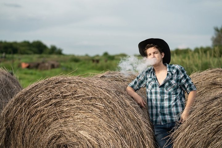 Portrait of a handsome young guy in a cowboy hat