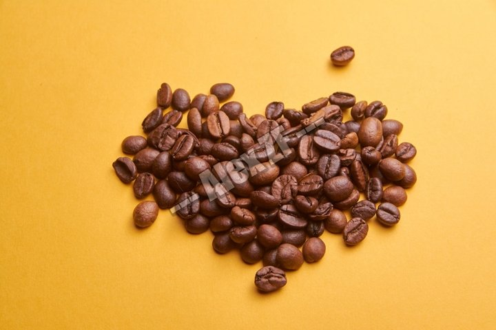 Heart of coffee beans on orange background