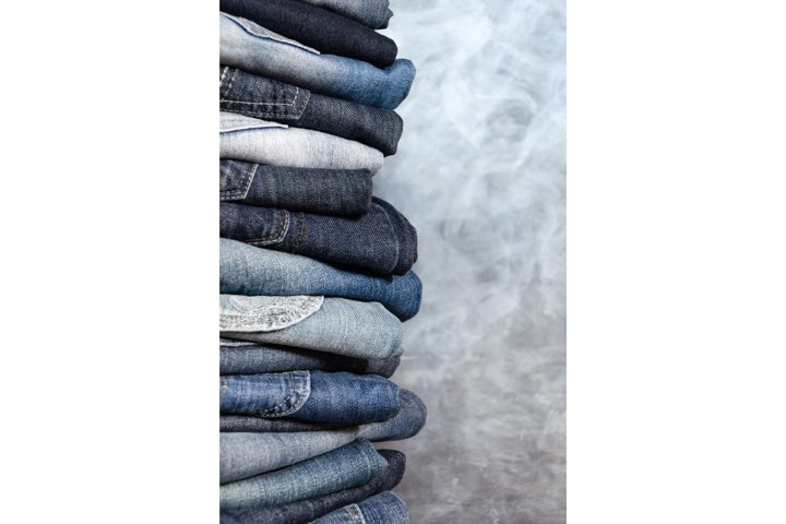 Stack of folded jeans on gray background. Fashion concept