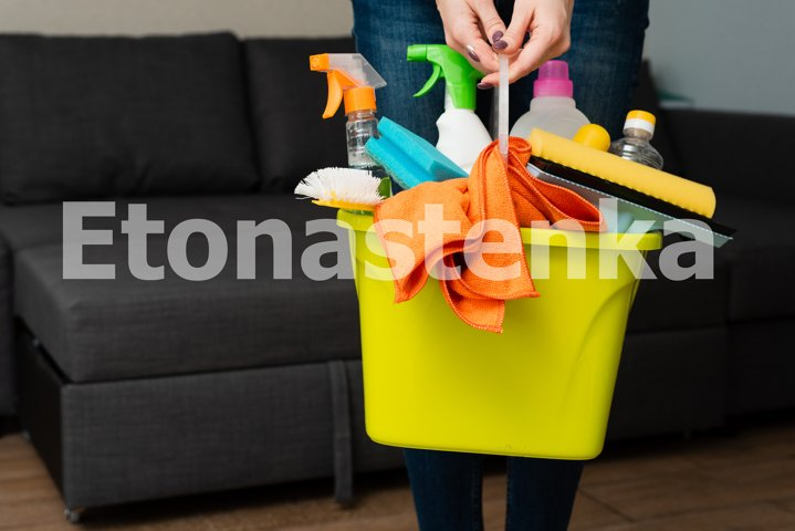 A girl is holding detergents in a bucket on the background.