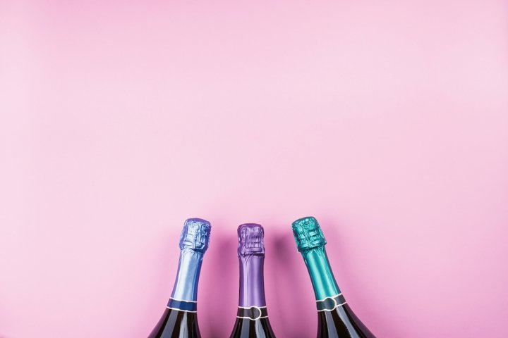Three champagne bottles on pink background