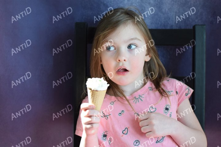 Girl 5 years old in a pink dress sits and eats ice cream.