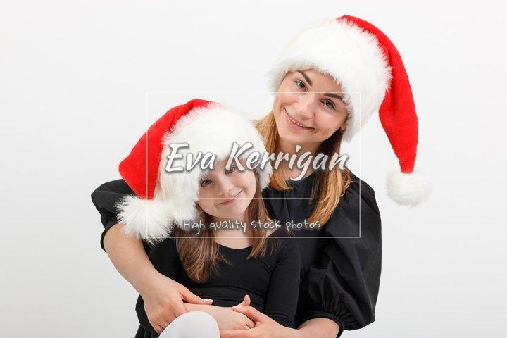 Mom in a santa hat hugs daughter.