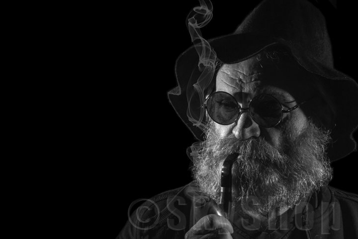 old man with a beard smokes a pipe