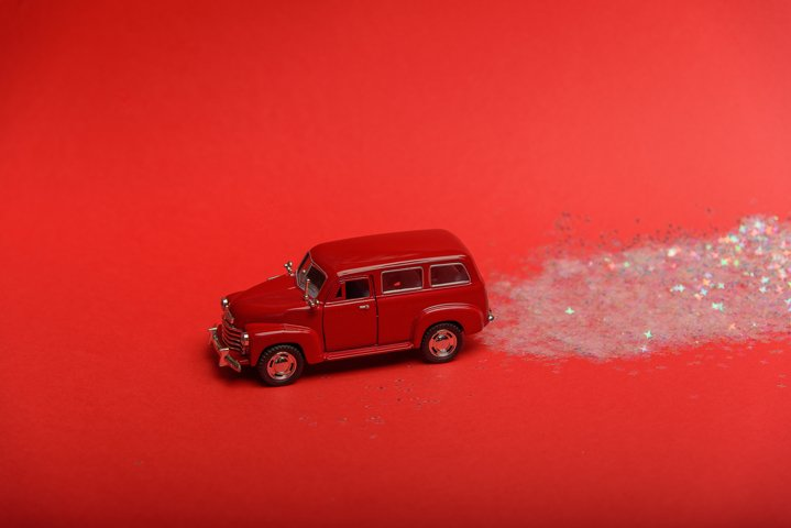 A toy car leaves a glowing trail of confetti on a red.