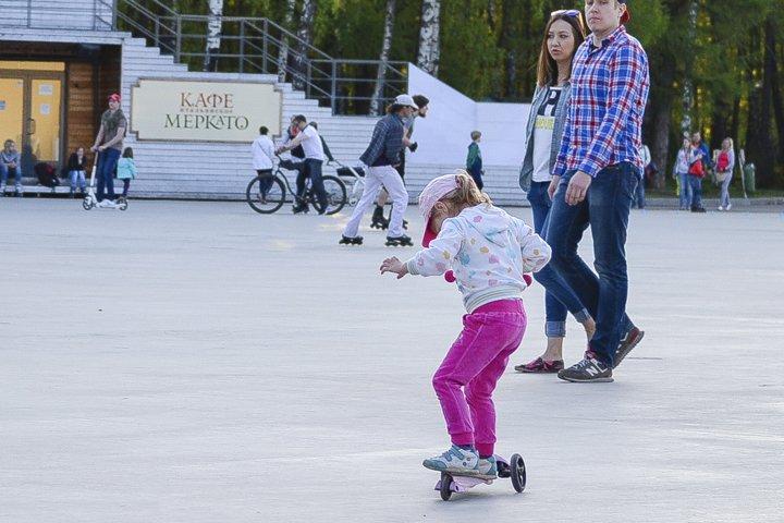 Little girl ride scooter in Sokolniki Park.