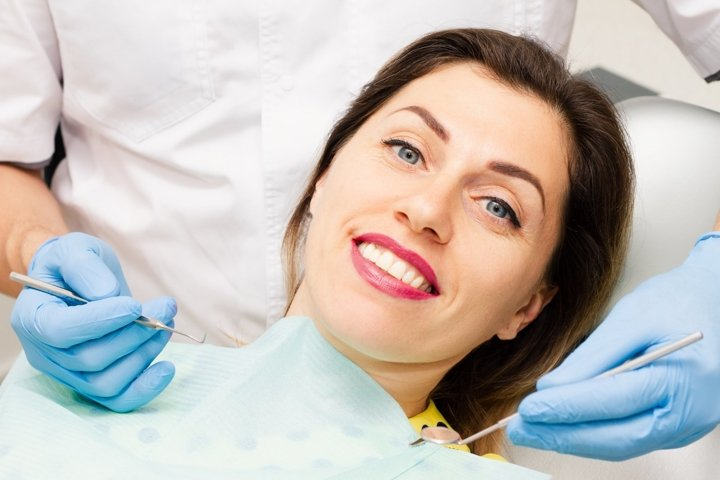 Young woman smiling at the dentist appointment.