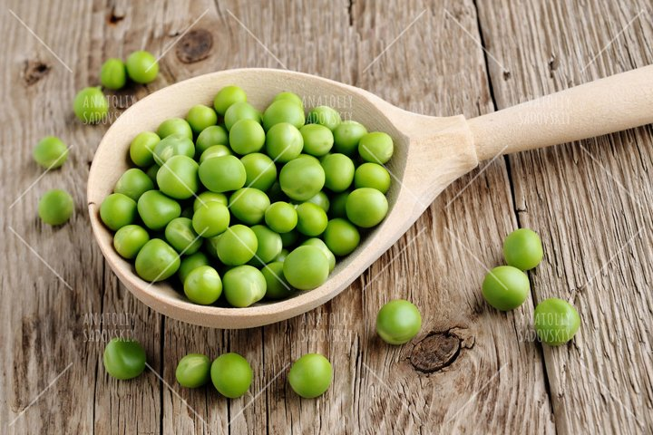 Fresh peas in spoon on wooden background