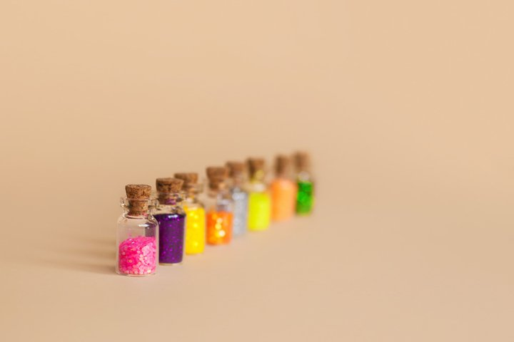 Colorful glitter in bottles on a beige background, isolated