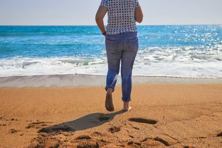 Girl in blue jeans running at the beach photo