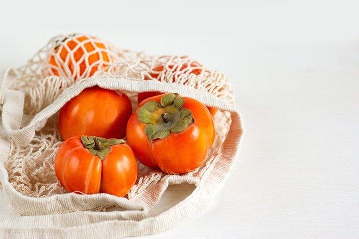 Persimmon close-up of a mesh shopping bag.