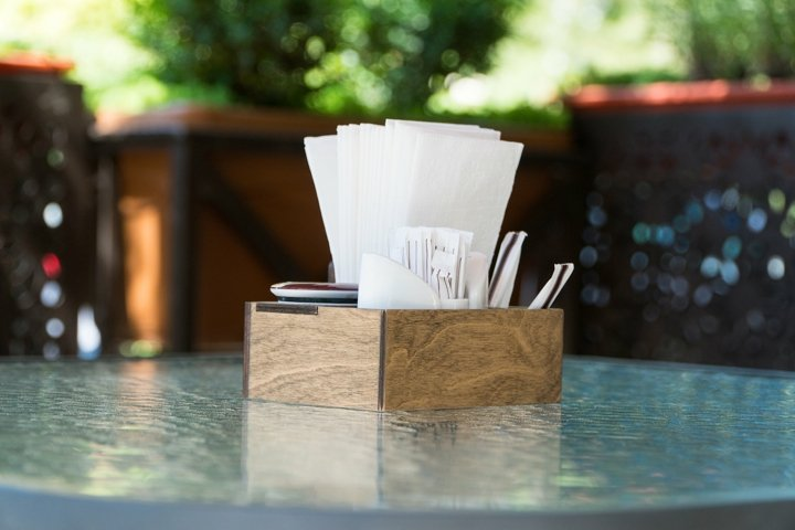 Box with paper napkins on a glass table. Outdoor summer cafe